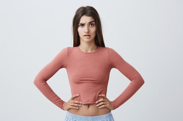 Retrato de uma jovem garota infeliz caucasiana com cabelos longos escuros na moda rosa top e calça azul desportiva, olhando com expressão de raiva, de mãos dadas na cintura, vendo o namorado
