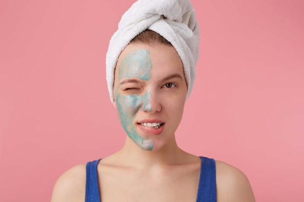 Retrato de uma jovem garota legal piscou com meia máscara facial, com uma toalha na cabeça após o banho, sorrindo e olhando.