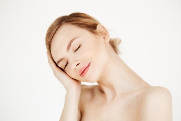 Retrato de uma jovem garota linda sorrindo com os olhos fechados, tocando o rosto. tratamento facial. cosmetologia de beleza e spa.