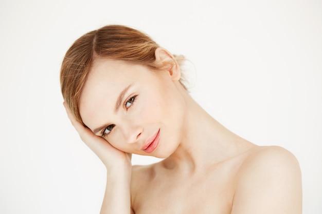 Retrato de uma jovem garota linda tocando o rosto. tratamento facial. produtos de beleza e cuidados com a pele.