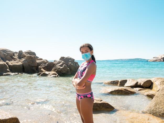 Retrato de uma jovem garota na praia usando uma máscara protetora para evitar a doença de coronavírus
