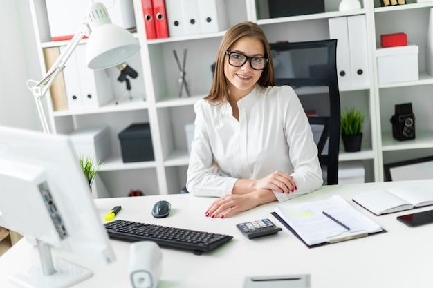 Retrato de uma jovem garota no escritório à mesa.