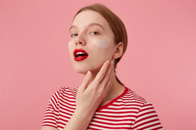 Retrato de uma jovem garota ruiva bonita com lábios vermelhos e com manchas sob os olhos, usa uma camiseta listrada vermelha, olha e toca a bochecha, ergue-se.