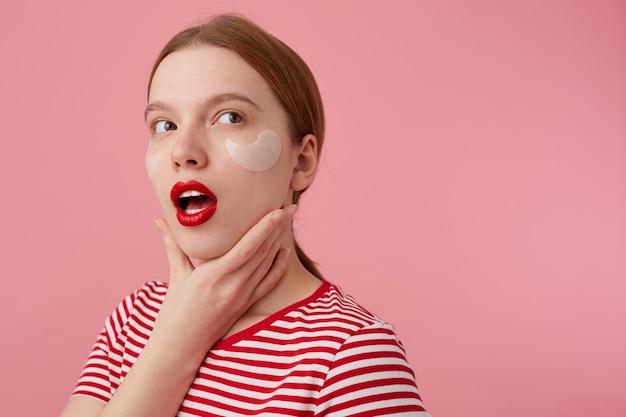 Retrato de uma jovem garota ruiva de pensamento fofo com lábios vermelhos e com manchas sob os olhos, usa uma camiseta listrada vermelha, desvia o olhar, toca a bochecha, fica de pé.