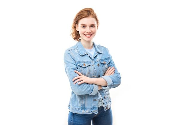 Retrato de uma jovem garota ruiva em um fundo branco e isolado em jeans. olha para a câmera