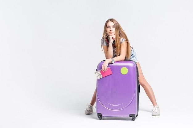 Retrato de uma jovem garota ruiva na moda em pé com uma mala e segurando o passaporte com os ingressos, sobre uma parede branca ou cinza