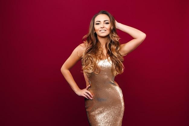 Retrato de uma jovem garota sedutora em um vestido dourado, tocando seu cabelo e olhando para a câmera contra o vermelho.