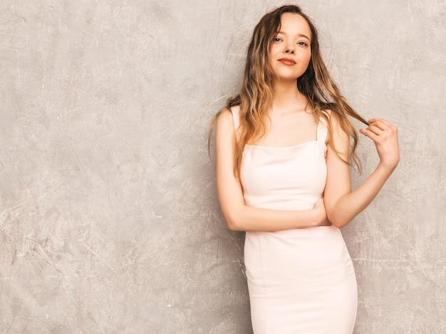 Retrato de uma jovem garota séria bonita na moda verão luz vestido rosa. mulher despreocupada sexy posando. modelo positivo se divertindo