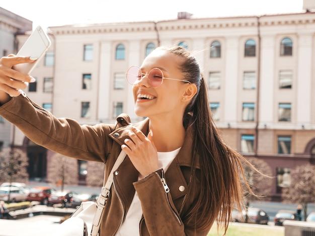 Retrato de uma jovem garota sorridente bonita jaqueta e jeans de verão hipster. modelo tomando selfie no smartphone. mulher fazendo fotos na rua. em óculos de sol