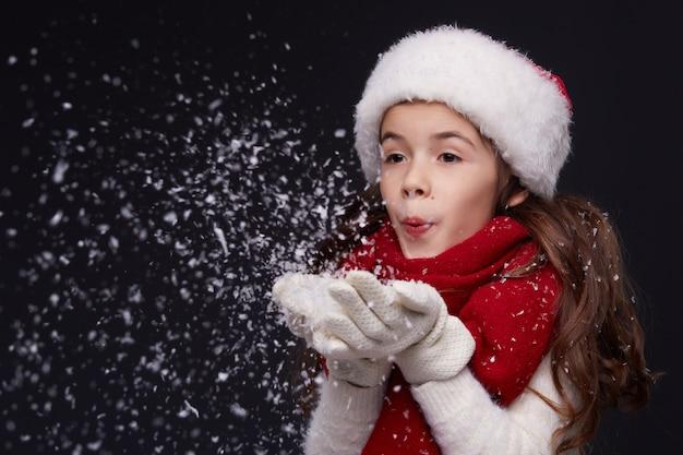 Retrato de uma jovem garota sorridente bonita no chapéu de papai noel vermelho sobre um fundo escuro