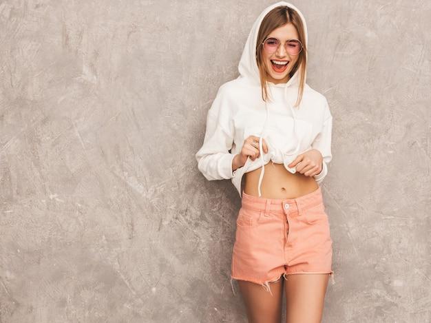 Retrato de uma jovem garota sorridente bonita roupas de esporte na moda verão. mulher despreocupada sexy posando. modelo positivo se divertindo em óculos de sol