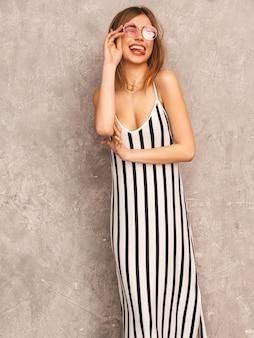 Retrato de uma jovem garota sorridente linda num vestido de zebra na moda verão. mulher despreocupada sexy posando. modelo positivo se divertindo em óculos de sol redondos. piscando