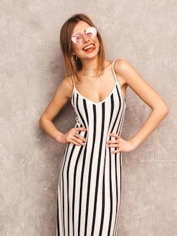 Retrato de uma jovem garota sorridente linda num vestido de zebra na moda verão. mulher despreocupada sexy posando. modelo positivo se divertindo em óculos de sol redondos