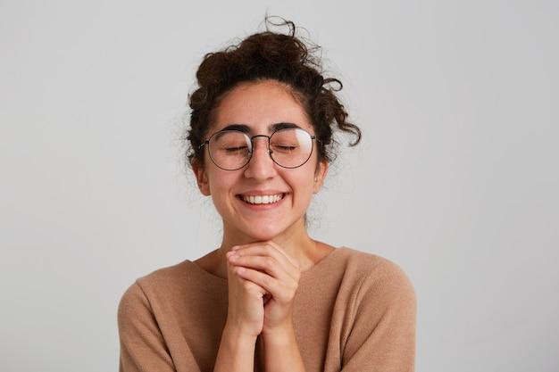Retrato de uma jovem georgiana linda e feliz com cabelo encaracolado usa um pulôver bege e óculos se sente feliz e olha para o lado isolado sobre uma parede branca