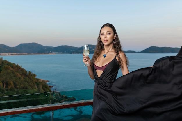Retrato de uma jovem graciosa em um lindo vestido de noite de chocolate com um enorme ornamento azul no pescoço e brincos compridos