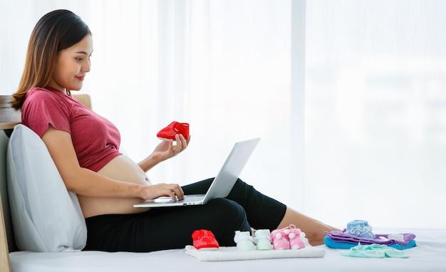 Retrato de uma jovem grávida asiática ativa, sentada em uma cama, segurando um sapato de bebê fofo, enquanto desfruta de usar e olhar para um laptop fazendo compras online.