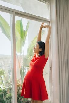 Retrato de uma jovem grávida se espreguiçando alegremente em pé na sala de estar iluminada pelo sol quente, copie o espaço