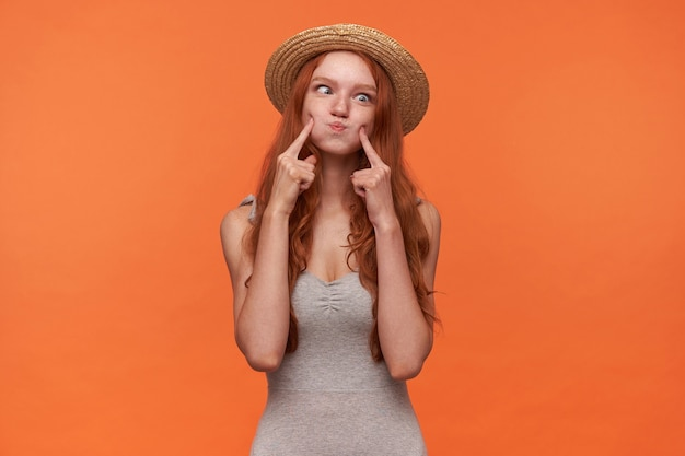 Retrato de uma jovem hilária com cabelo ruivo londrino se divertindo com um fundo laranja, estufando as bochechas e apertando os olhos para a câmera, vestindo camisa cinza e chapéu de veleiro