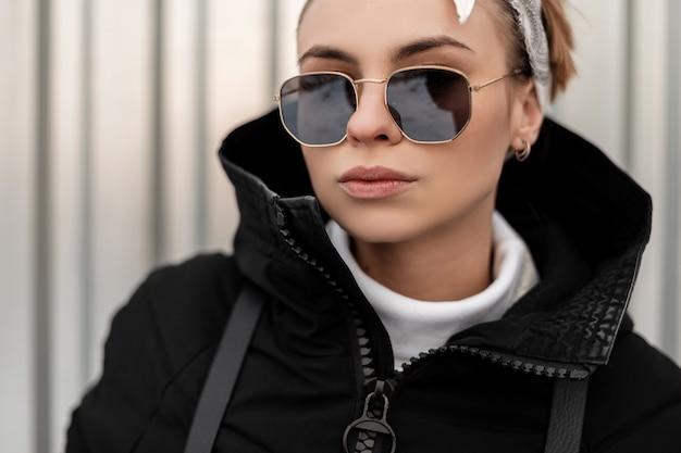 Retrato de uma jovem hippie sexy em elegantes óculos de sol em uma bandana com uma elegante jaqueta de inverno perto de uma parede de metal cinza. garota americana.