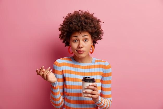 Retrato de uma jovem indecisa e sem noção encolhe os ombros e se sente desnorteada, bebe café para viagem e conversa com alguém vestido com um macacão listrado casual isolado sobre a parede rosa