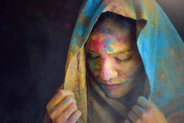 Retrato de uma jovem indiana celebrando o festival de cores holi. retrato do rosto de um jovem indiano pintado