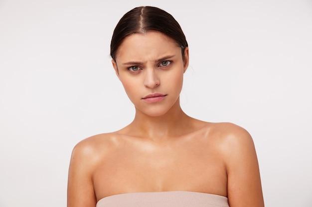 Retrato de uma jovem indignada mulher de cabelos escuros, olhos verdes e maquiagem natural, olhando severamente e franzindo a testa, em pé