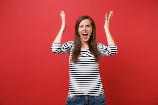 Retrato de uma jovem irritada com raiva em roupas listradas, gritando, levantando-se e estendendo as mãos