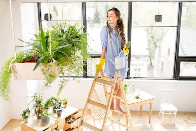 Retrato de uma jovem jardineira em pé com um regador na escada no laranjal