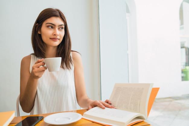 Retrato de uma jovem latina, desfrutando e bebendo uma xícara de café na cafeteria. conceito de estilo de vida.
