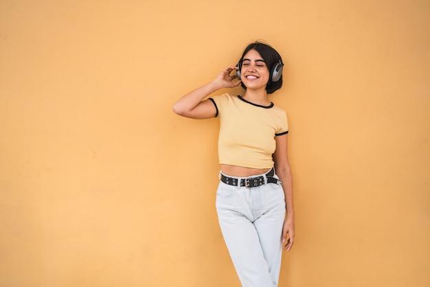 Retrato de uma jovem latina ouvindo música com fones de ouvido contra o espaço amarelo. conceito urbano.