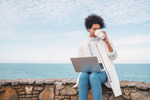 Retrato de uma jovem latina usando seu laptop e bebendo uma xícara de café enquanto está sentado contra o mar