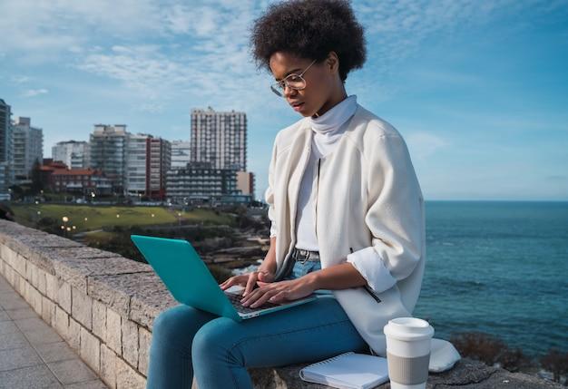 Retrato de uma jovem latina usando seu laptop enquanto está sentada contra o mar