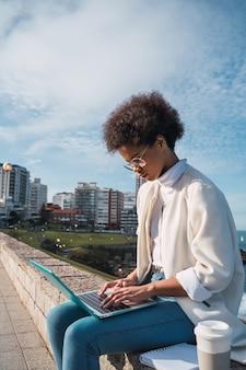 Retrato de uma jovem latina usando seu laptop enquanto está sentado ao ar livre na rua. conceito urbano e de tecnologia.
