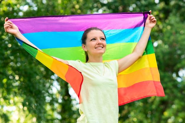 Retrato de uma jovem lésbica feliz orgulhosa, linda garota está acenando a bandeira gay de cor lgbt de arco-íris em um dia ensolarado de verão em fundo natural. comunidade lgbt, conceito de igualdade de relações homossexuais