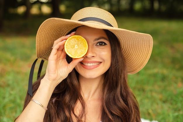 Retrato de uma jovem linda com dentes brancos, um lindo sorriso com um chapéu de palha segura um limão perto de seu rosto.