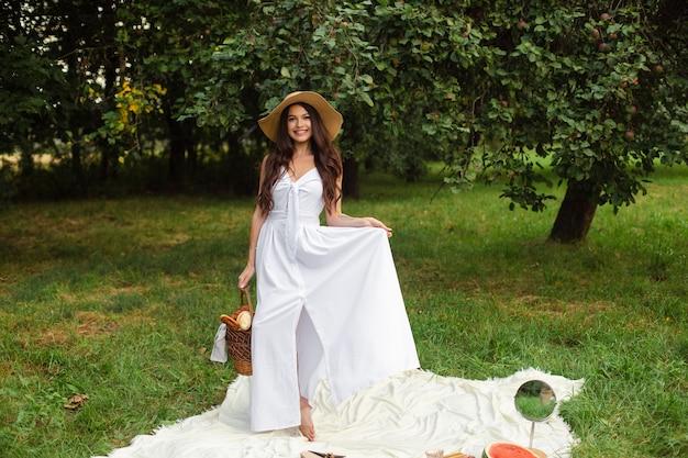 Retrato de uma jovem linda com dentes brancos, um lindo sorriso em um chapéu de palha e um vestido longo branco tem um piquenique no jardim.
