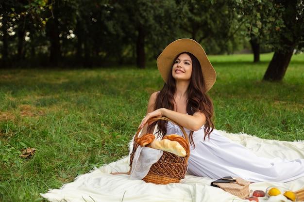 Retrato de uma jovem linda com dentes brancos, um lindo sorriso em um chapéu de palha, fazer um piquenique no jardim.