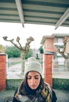 Retrato de uma jovem linda com os olhos fechados, usando chapéu e lenço em um dia chuvoso de outono