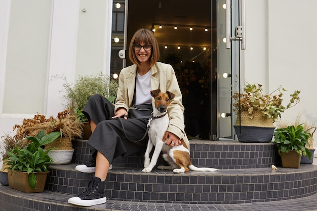 Retrato de uma jovem linda em óculos de sol, alegremente sentada nas escadas na rua da cidade com seu pequeno cachorro fofo raça jack russell terrier