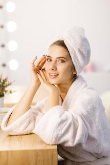 Retrato de uma jovem linda em um manto branco e uma toalha na cabeça