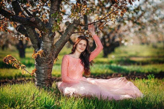 Retrato de uma jovem linda em um pomar de primavera