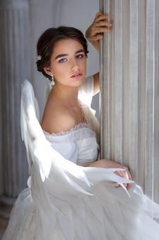 Retrato de uma jovem linda em um vestido branco e asas de anjo, em pé com um olhar suplicante no contexto de uma parede com colunas e flores