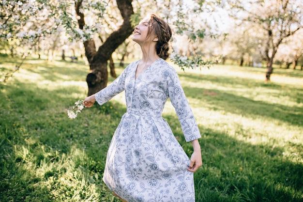 Retrato de uma jovem linda em um vestido de renda branca no jardim de maçãs, na copa da árvore, com os dedos perto da boca