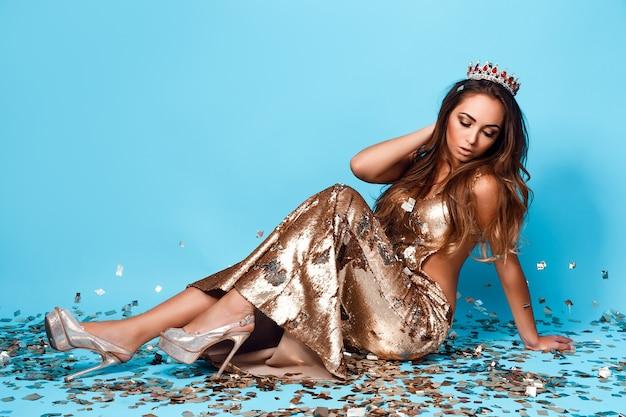 Retrato de uma jovem linda em um vestido dourado e coroa posando em fundo azul com confete