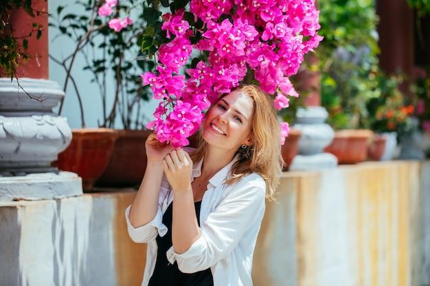 Retrato de uma jovem linda em uma camisa branca com flores rosa buganvílias no jardim.