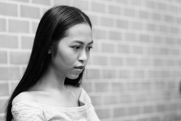 Retrato de uma jovem linda garota asiática em uma parede de tijolos ao ar livre em preto e branco