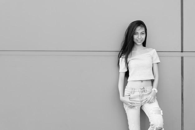 Retrato de uma jovem linda garota asiática na parede de concreto ao ar livre em preto e branco