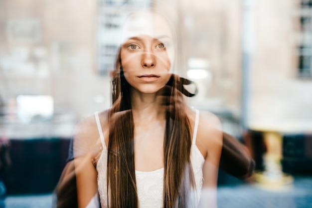 Retrato de uma jovem linda garota morena romântica com cabelo comprido posando atrás de um vidro.