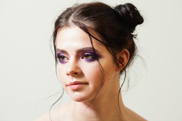 Retrato de uma jovem linda morena com uma linda maquiagem fashion nos cílios