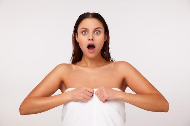 Retrato de uma jovem linda morena espantada com o cabelo molhado, olhando para a câmera com os olhos arregalados e a boca aberta enquanto posava sobre um fundo branco depois do banho
